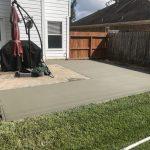 shaped concrete patio in backyard